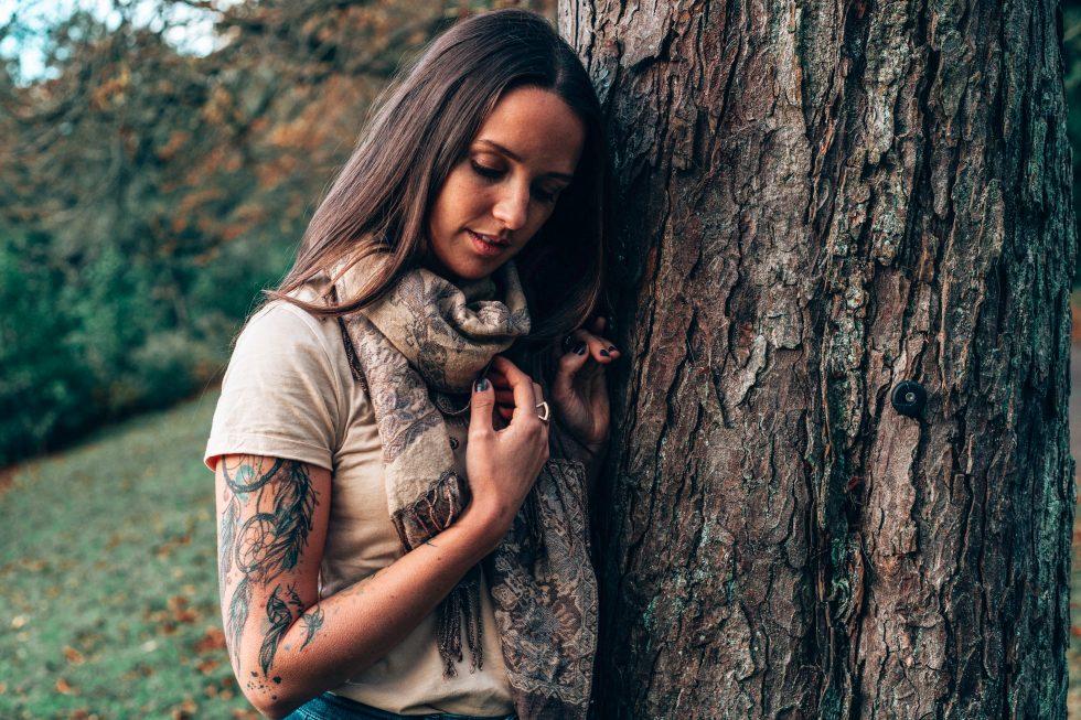 Frau steht am Baum und lächelt