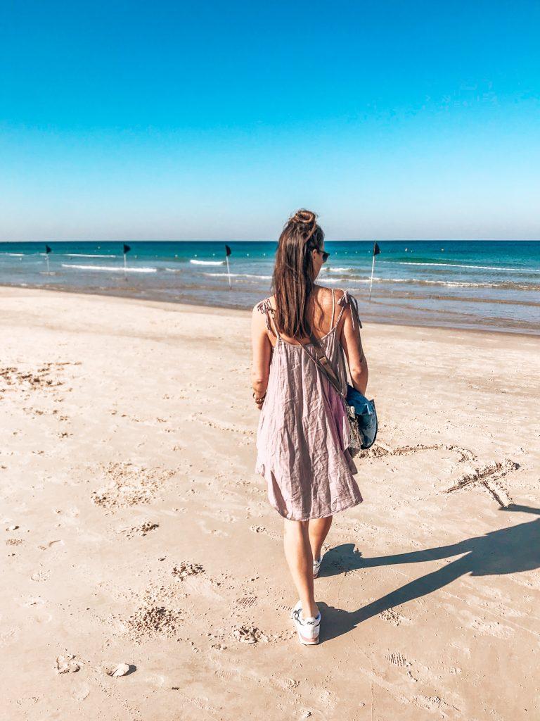 Frau spaziert Richtung Meer